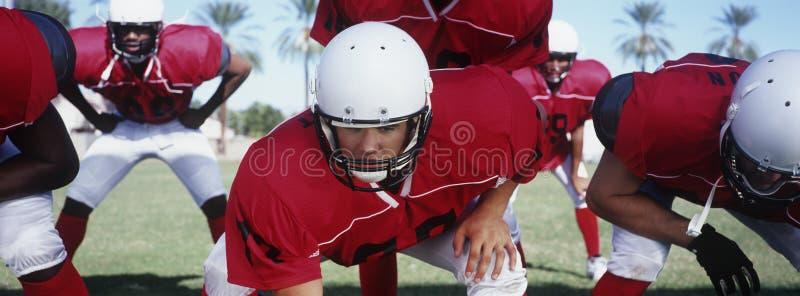Amerikanska fotbollsspelare på startpositionen royaltyfria foton