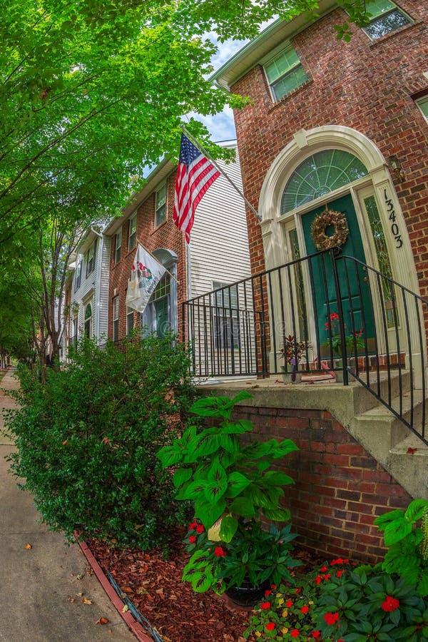 Amerikanska och dekorativa flaggor framme av typiska amerikanska hus arkivfoto