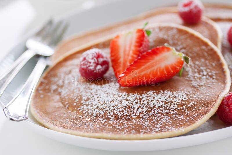 Amerikanska pannkakor för hemlagad kärnmjölk med den nya jordgubben och hallonet på en vit platta royaltyfria foton
