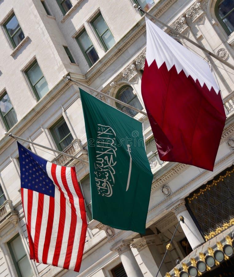 Amerikanska saudierQatar flaggor arkivbild