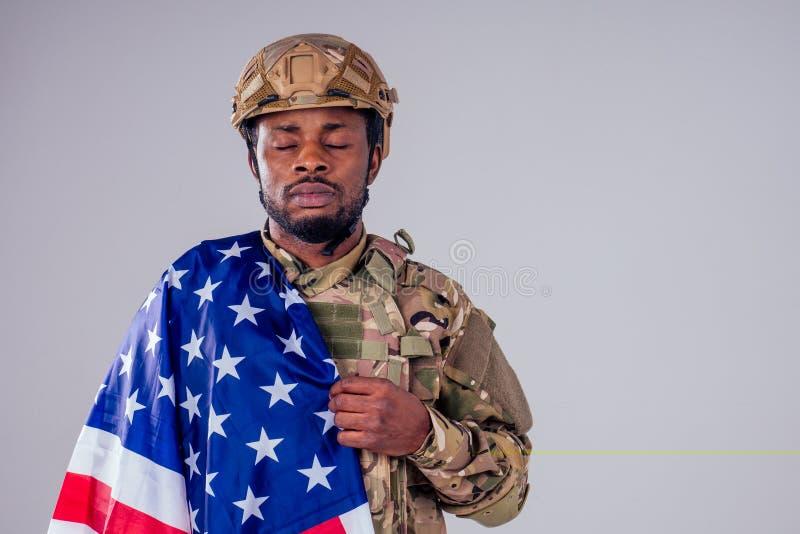 Amerikanska soldat med hopfällda vapen i vit studio royaltyfri fotografi