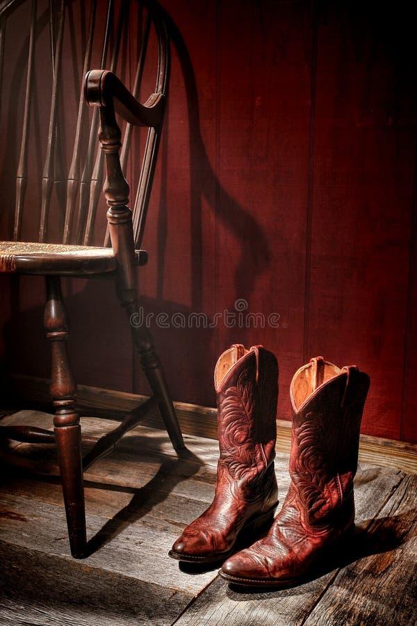 Amerikanska västra rodeocowgirlkängor och gammal stol arkivbilder