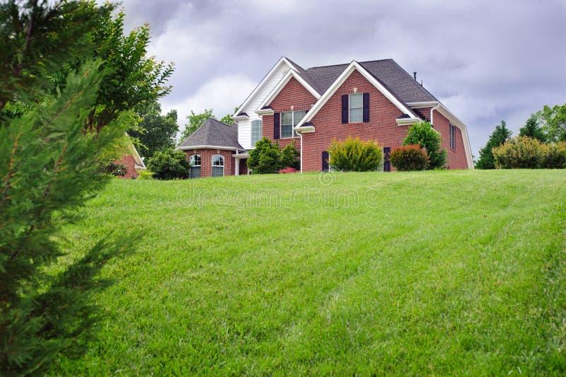 Amerikanskt hus med härlig grön gräsmatta royaltyfri foto