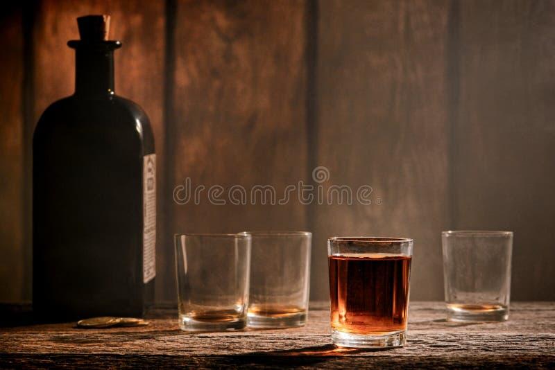 Amerikanskt västra legendwhiskyexponeringsglas på västra stång royaltyfri foto