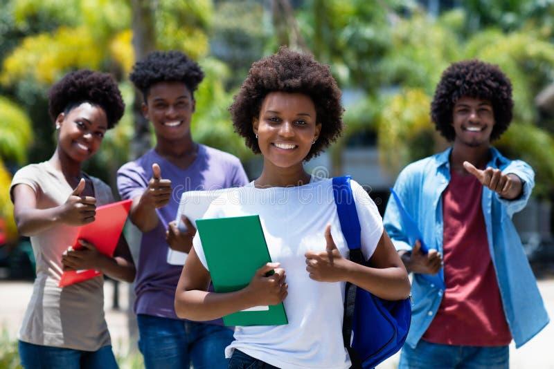 Amerlcan weiblicher Hochschulstudent des erfolgreichen Afrikaners mit Gruppe Afroamerikanerstudenten stockbilder