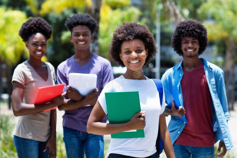 Amerlcan weiblicher Hochschulstudent des hübschen Afrikaners mit Gruppe Afroamerikanerstudenten stockbild