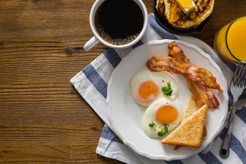 Amerykański śniadanie z pogodną stroną w górę jajek, bekonu, grzanki, blinów, kawy i soku, zdjęcia royalty free