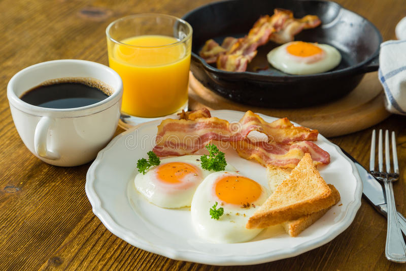 Amerykański śniadanie z pogodną stroną w górę jajek, bekonu, grzanki, blinów, kawy i soku, obrazy royalty free