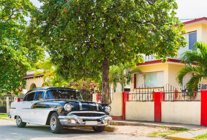 Amerykański czarny bielu rocznika 1956 samochód parkujący w sidestreet przed domem w Varadero Kuba zdjęcia stock