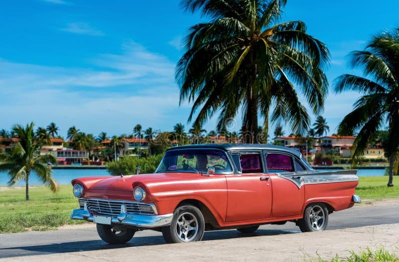 Amerykański czerwony Ford klasyczny samochód z czerń dachem parkującym pod niebieskim niebem blisko plaży w Hawańskim Kuba, Seria fotografia stock