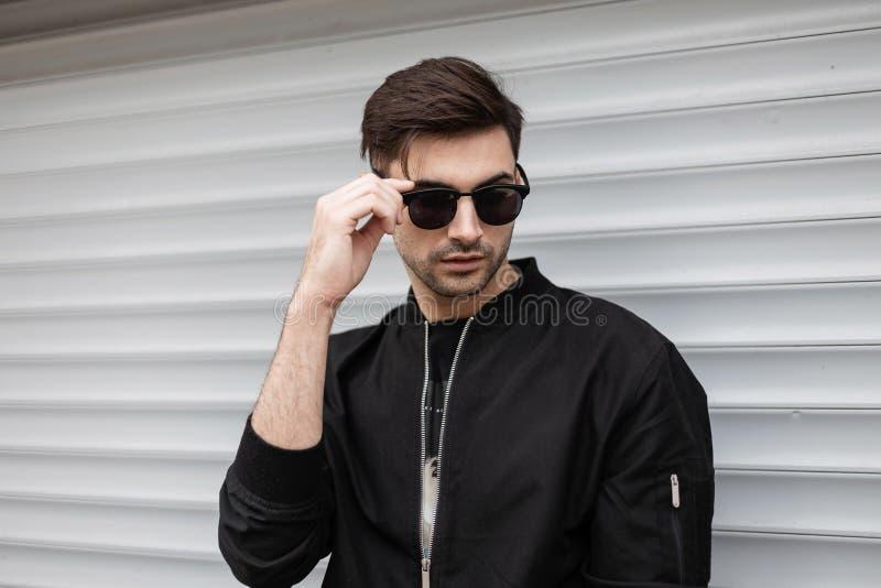Amerykański modnisia młody człowiek w czarnej eleganckiej kurtce stoi modnych okulary przeciwsłonecznych i prostuje blisko kruszc obraz royalty free