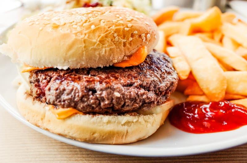 Amerykańskiego sera hamburger z Złotymi Francuskimi dłoniakami fotografia royalty free