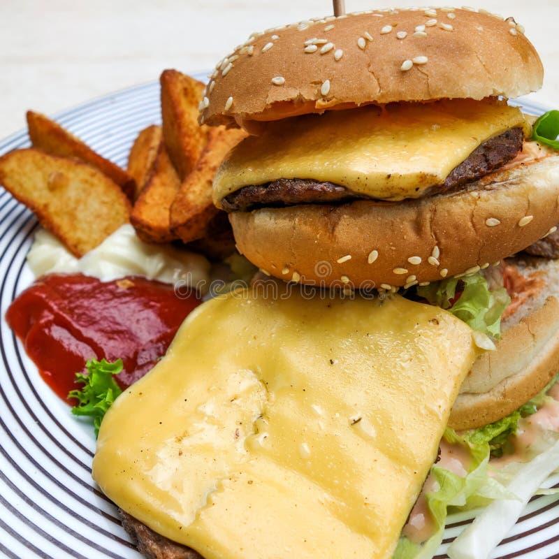 Amerykańskiego sera hamburger z Złotymi Francuskimi dłoniakami zdjęcie royalty free