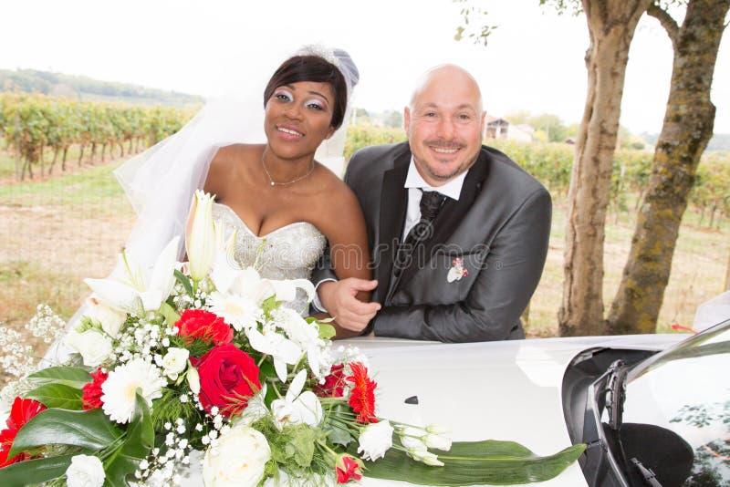 Amerykańskiej pary afrykańska panna młoda pozuje na ślubnym samochodzie z caucasian fornalem zdjęcie royalty free