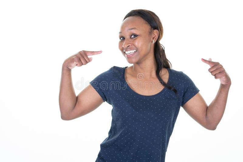 Amerykanin afrykańskiego pochodzenia ładna młoda kobieta patrzeje ufny z uśmiechem na twarzy ono wskazuje z palcami nad odosobnio obraz royalty free