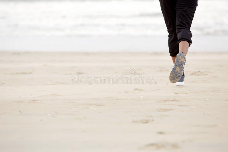 Amerykanin afrykańskiego pochodzenia żeński bieg na plaży z gym butami zdjęcie stock