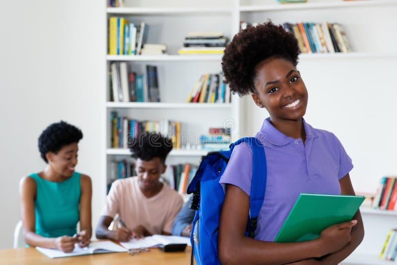 Amerykanin afrykańskiego pochodzenia żeński młody dorosły z uczniami i nauczycielem zdjęcie royalty free