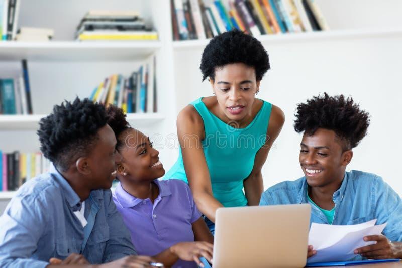 Amerykanin afrykańskiego pochodzenia żeński nauczyciel z uczniami obraz stock