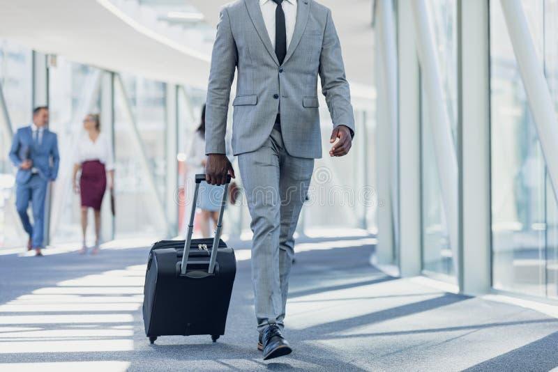 Amerykanin afrykańskiego pochodzenia biznesmena odprowadzenie w korytarzu z walizką w nowożytnym biurze obrazy royalty free