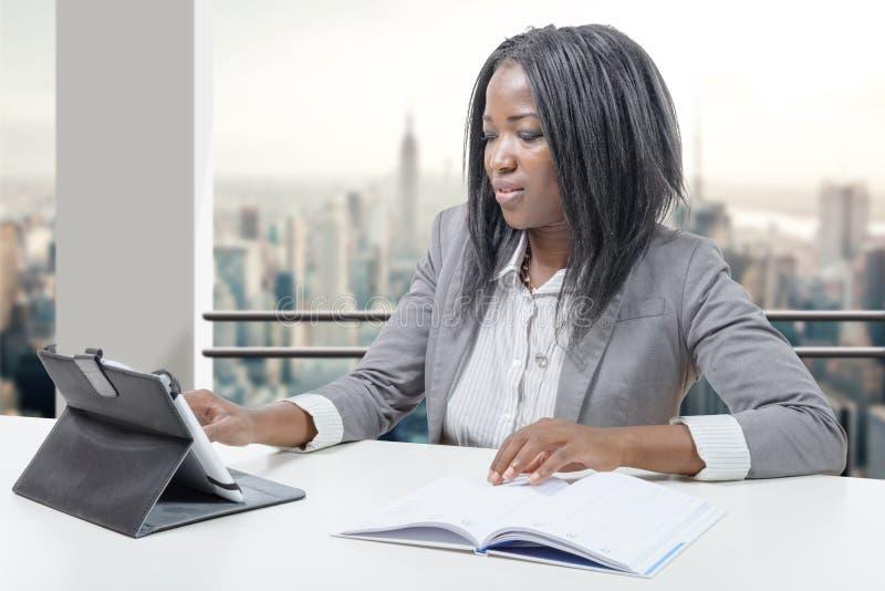 Amerykanin afrykańskiego pochodzenia biznesowa kobieta pracuje z pastylką zdjęcia royalty free