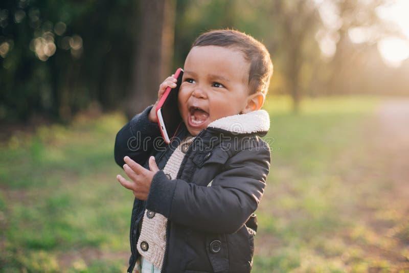 Amerykanin Afrykańskiego Pochodzenia chłopiec bawić się z telefonem komórkowym zdjęcia royalty free