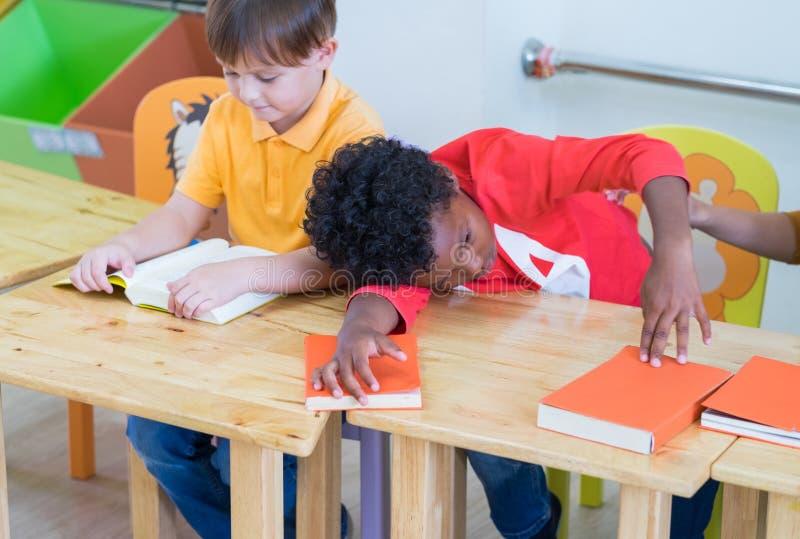 Amerykanin afrykańskiego pochodzenia chłopiec dzieciak z smucenie emoci obsiadaniem w classro fotografia stock