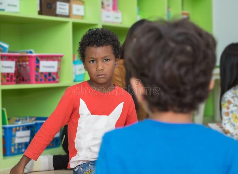 Amerykanin afrykańskiego pochodzenia chłopiec gniewna i patrzeje przyjaciela w szkolnym libra zdjęcia royalty free