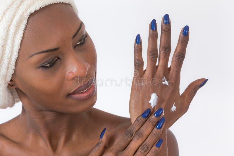 Amerykanin Afrykańskiego Pochodzenia dziewczyna stosuje twarzowego skincare produkt fotografia stock