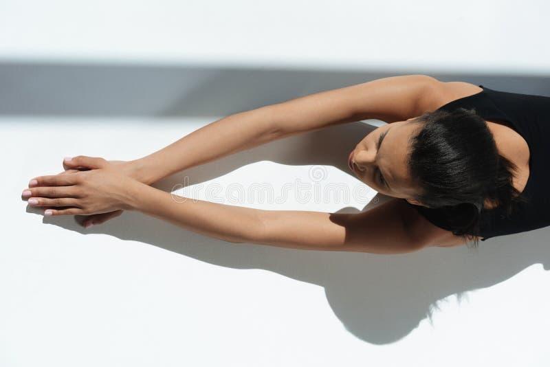 Amerykanin afrykańskiego pochodzenia elegancka zmysłowa kobieta relaksuje i sunbathing w czarnym bodysuit fotografia stock