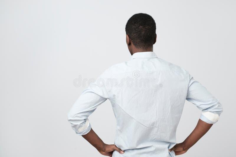 Amerykanin afrykańskiego pochodzenia facet w białej koszula, obraca z powrotem kamera gdy obraża obraz stock
