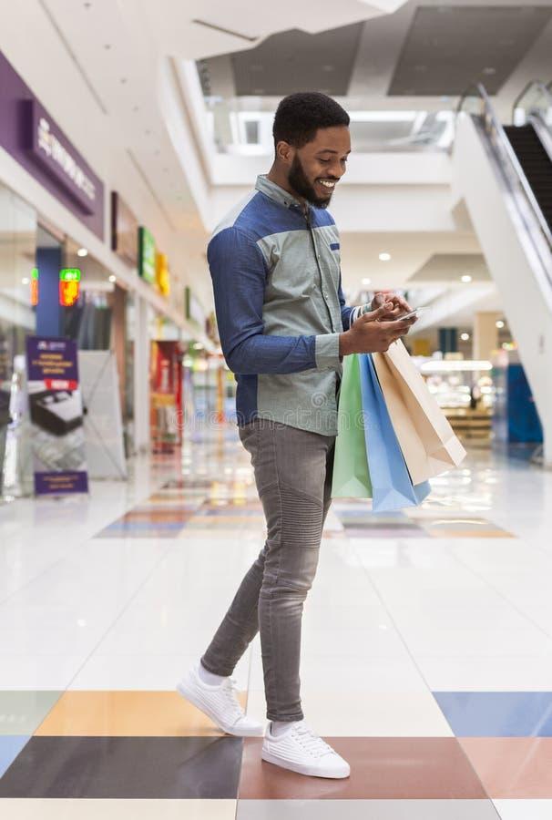 Amerykanin afrykańskiego pochodzenia facet z telefonem komórkowym whriting dobrego rewiew obrazy stock