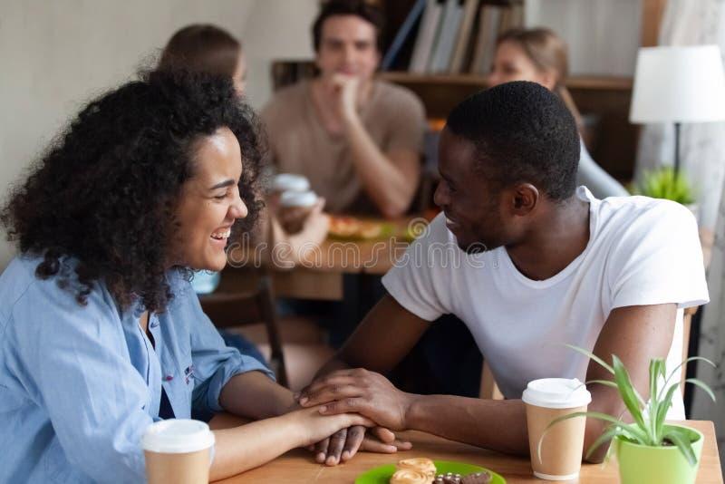 Amerykanin afrykańskiego pochodzenia faceta obsiadanie przy kawiarnią z szczęśliwą młodą kobietą zdjęcia royalty free