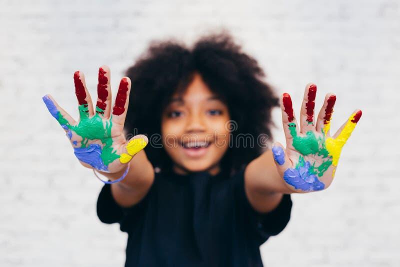 Amerykanin Afrykańskiego Pochodzenia figlarnie i kreatywnie dzieciak dostaje ręki brudzimy z wiele kolorami zdjęcie stock