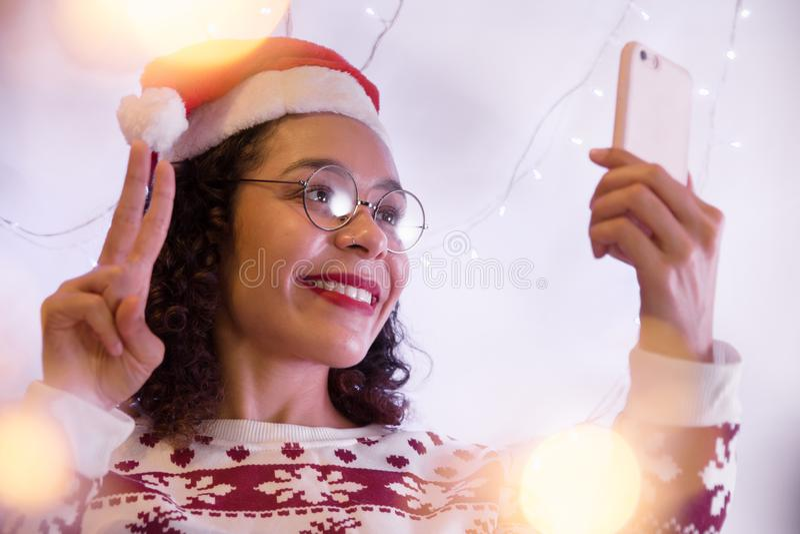 Amerykanin Afrykańskiego Pochodzenia kobieta jest ubranym Santa kapelusz u i boże narodzenie pulower zdjęcie stock