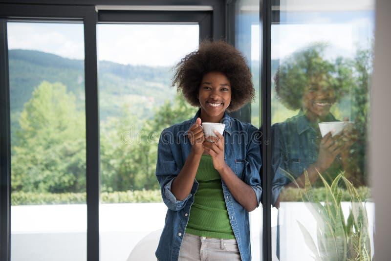 Amerykanin Afrykańskiego Pochodzenia kobieta pije kawowy przyglądającego out okno zdjęcia stock