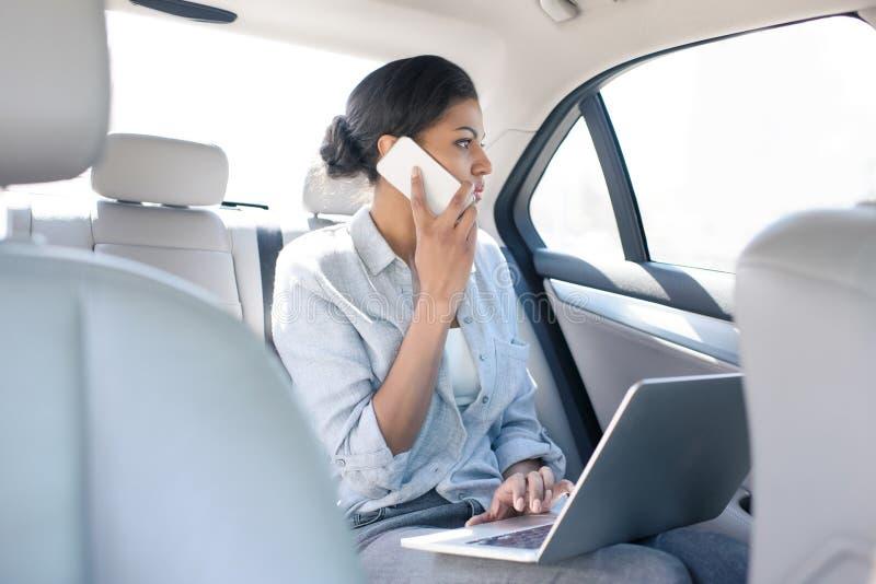 Amerykanin afrykańskiego pochodzenia kobieta pracuje z laptopem i smartphone w taxi zdjęcie royalty free