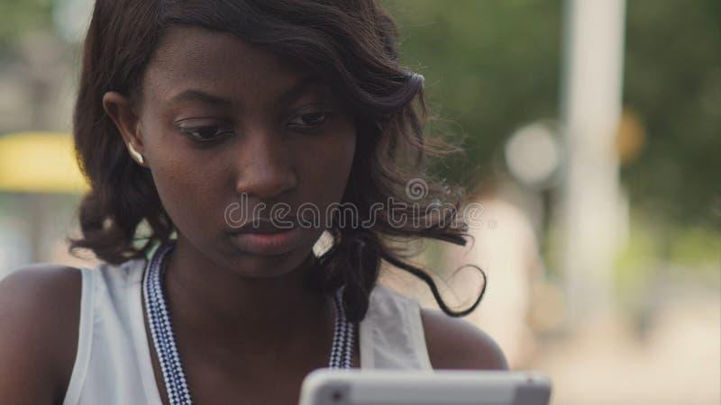 Amerykanin afrykańskiego pochodzenia kobieta używa jej pastylkę obraz stock