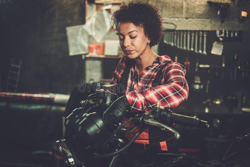 Amerykanin afrykańskiego pochodzenia kobiety mechanik naprawia motocykl w warsztacie fotografia royalty free