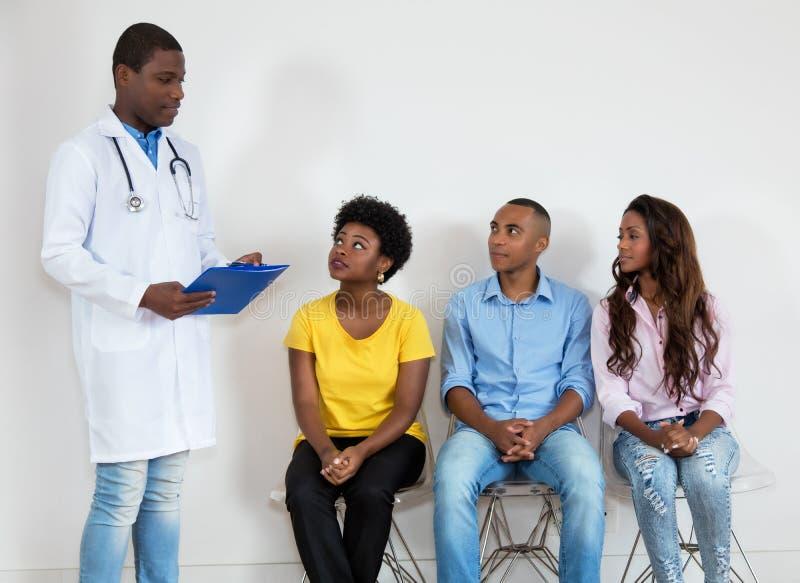 Amerykanin afrykańskiego pochodzenia lekarka z pacjentami przy poczekalnią zdjęcie royalty free