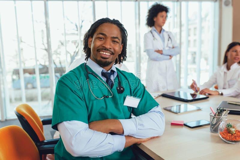 Amerykanin afrykańskiego pochodzenia lekarz medycyny z kolegami w tle obrazy royalty free