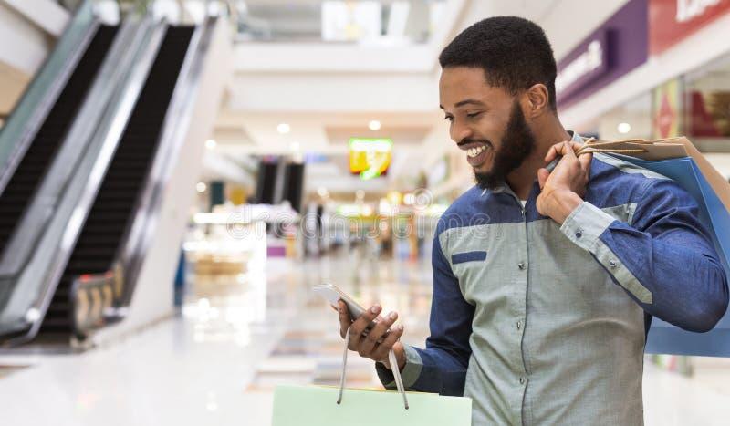 Amerykanin afrykańskiego pochodzenia mężczyzna z torbami na zakupy używać telefon komórkowego obraz royalty free