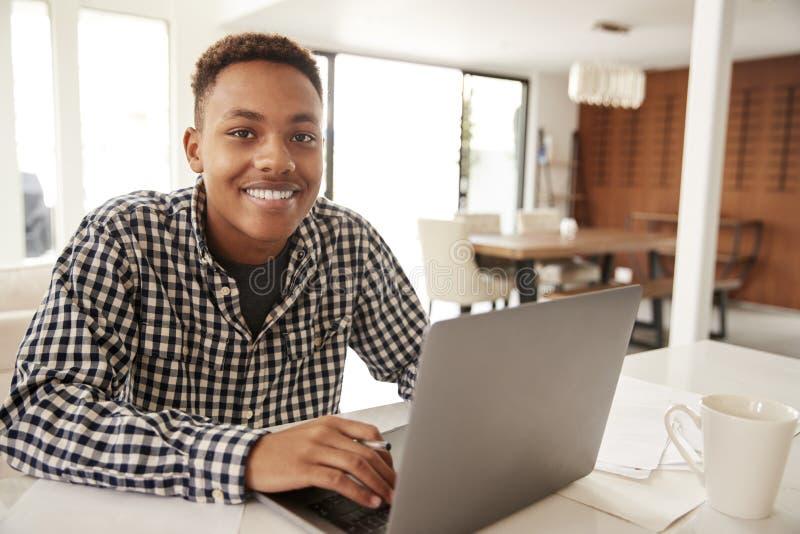 Amerykanin Afrykańskiego Pochodzenia męski nastolatek używa laptop ono uśmiecha się kamera w domu, zakończenie w górę obrazy royalty free