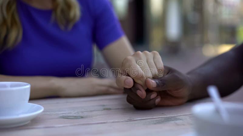 Amerykanin afrykańskiego pochodzenia męskiego mienia caucasian dziewczyny wręczają, wspierają i kochają, obrazy stock