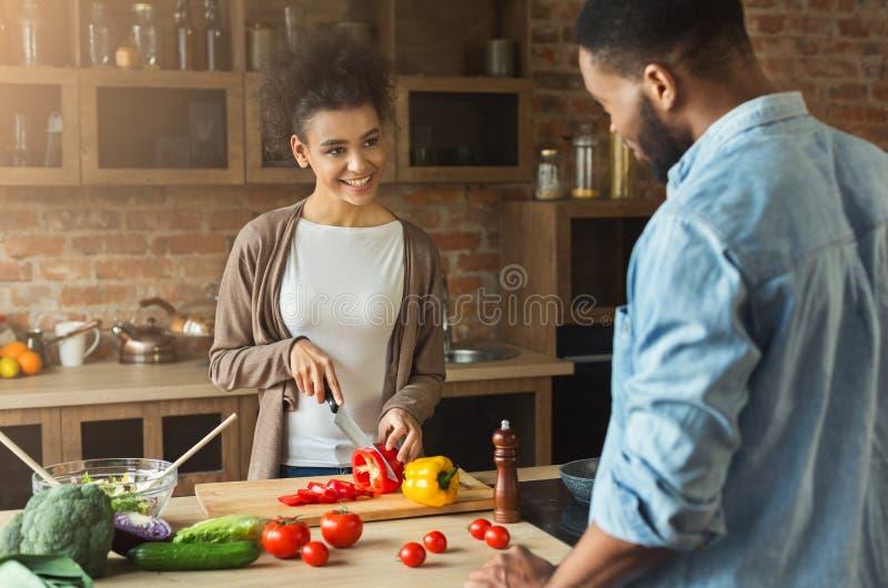 Amerykanin afrykańskiego pochodzenia młoda kobieta patrzeje chłopaka podczas gdy gotujący sałatki fotografia stock