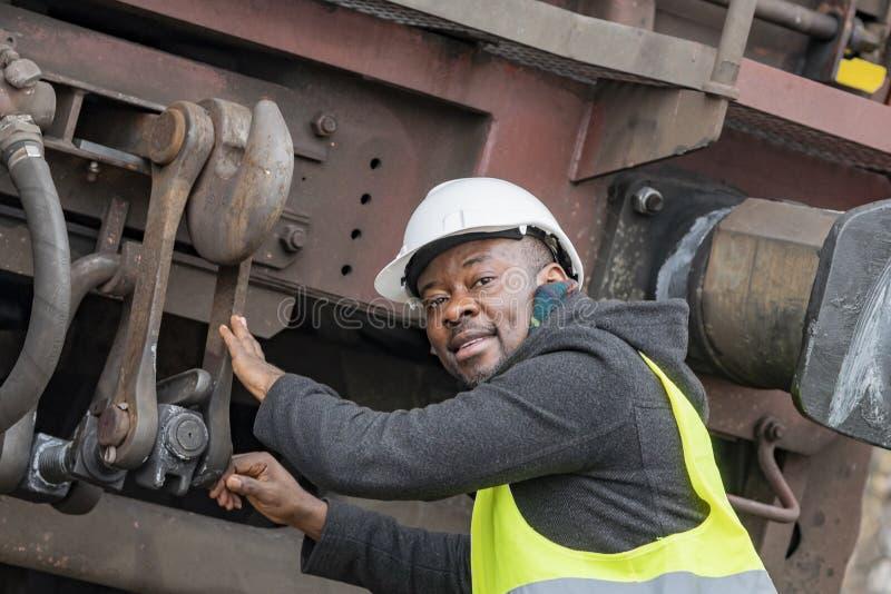 Amerykanin Afrykańskiego Pochodzenia mechanik sprawdza przekładnia pociąg obraz stock