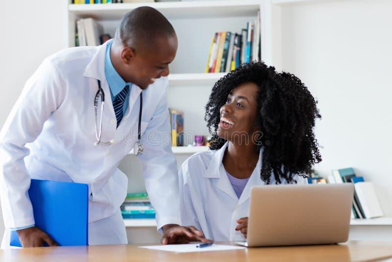 Amerykanin afrykańskiego pochodzenia naczelny lekarz z młodą kobiety lekarką przy pracą fotografia royalty free
