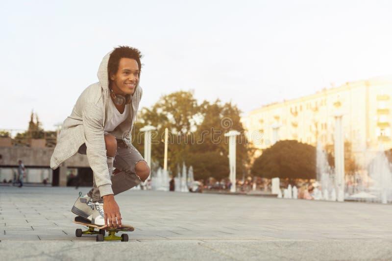 Amerykanin Afrykańskiego Pochodzenia Nastoletni facet Jeździć na deskorolce na lato wieczór fotografia stock