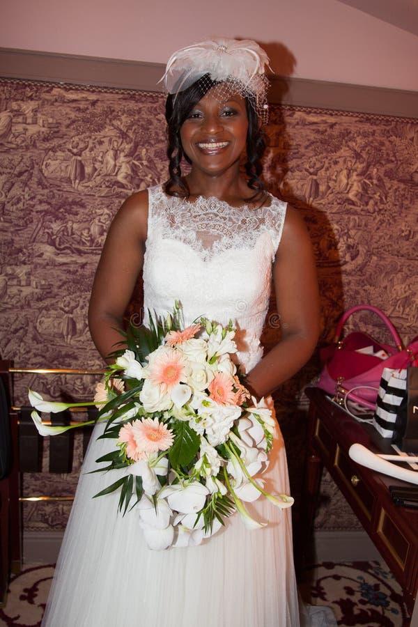 Amerykanin afrykańskiego pochodzenia panna młoda ono uśmiecha się przy kamery mienia bukietem zdjęcie royalty free