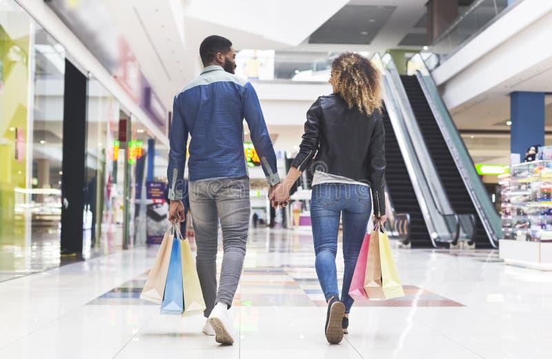 Amerykanin afrykańskiego pochodzenia para chodzi centrum handlowym z torbami na zakupy obraz stock