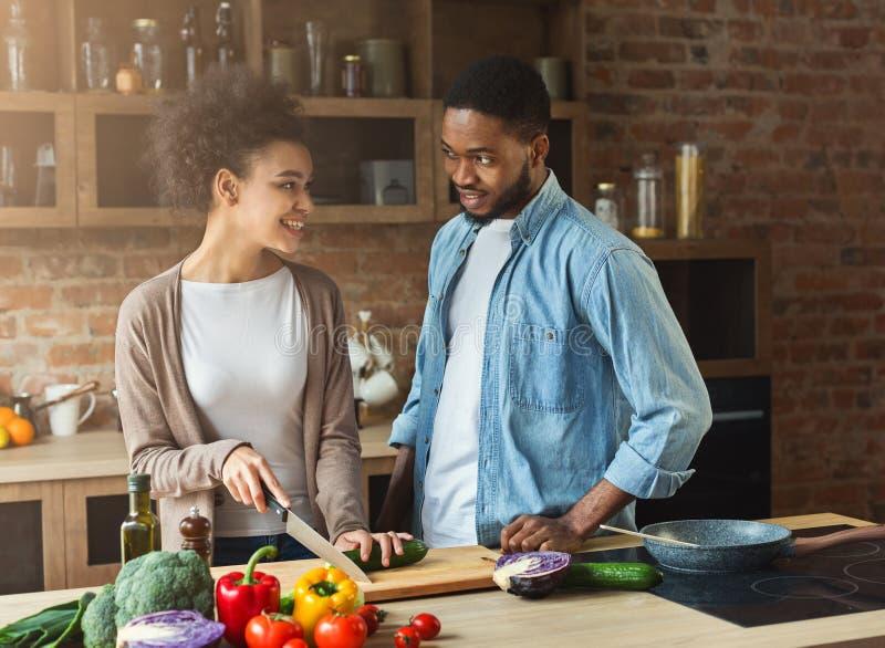 Amerykanin afrykańskiego pochodzenia para gotuje zdrowego jedzenie wpólnie obraz royalty free
